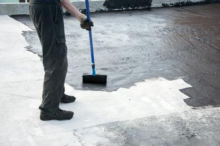 Roofer betún pintura trabajador praimer en la superficie de concreto por el rodillo de cepillo, para la impermeabilización.