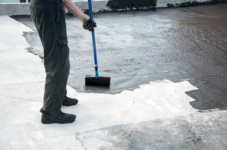 waterproofing: Roofer worker painting  bitumen praimer at concrete surface by the roller brush,  for waterproofing.