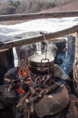 soup kettle: Cooking in field conditions, boiling pot at the campfire on picnic, mountains,