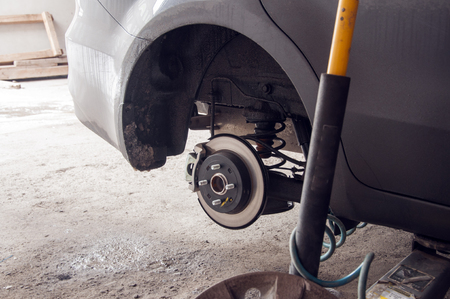 disassembly: repairing suspension of lifted automobile at auto repair garage shop station Stock Photo