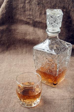 bourbon: Carafe and glass of whisky, whiskey bourbon on a burlap, sacks background Stock Photo