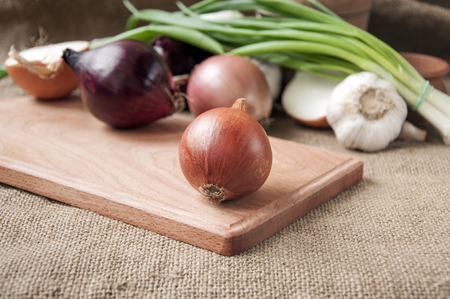 materia: Various onions on a board on a background sacking, burlap