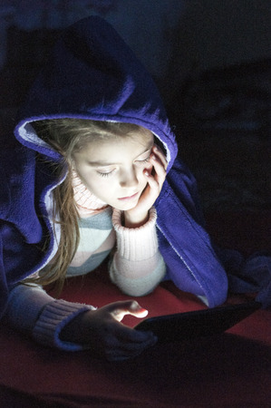 fell: Adorable Little girl  playing tablet pc in bedroom at night, and fell asleep.