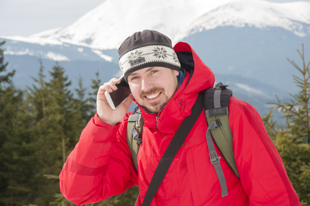 Hiker talking on the smartphone in the winter mountains. Mobile communications in the mountains
