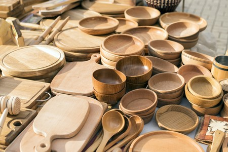 wood turning: Handmade wooden, vintage kitchen utensils for sale at the market. Various wooden kitchen tools. Different wooden tableware. Wooden stand under the hot pan.