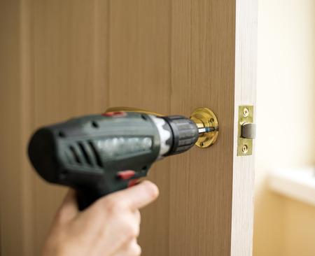 Installazione di serratura con un cacciavite a. Carpenter al momento dell'installazione serratura con trapano elettrico in porta di legno.