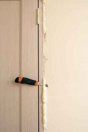 excess: Master knife cuts off excess foam. Installation of doors using polyurethane foam mounting. Cylinder Foam.