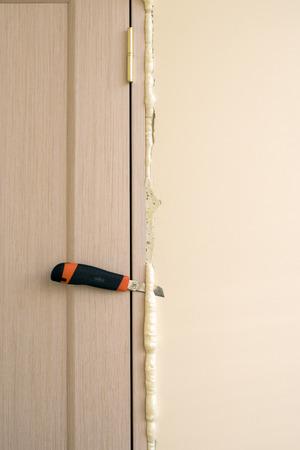 pu foam: Master knife cuts off excess foam. Installation of doors using polyurethane foam mounting. Cylinder Foam.
