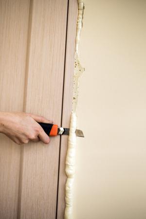 Master knife cuts off excess foam. Installation of doors using polyurethane foam mounting. Cylinder Foam.