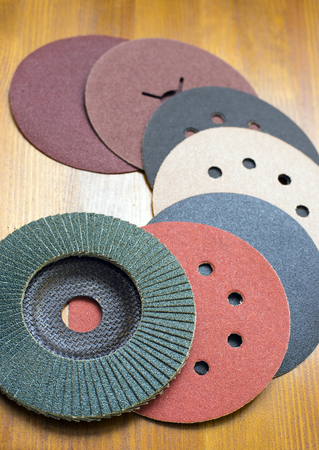 buffing: Abrasive disks for metal and stone,wood grinding, cutting. Set of abrasive materials on wooden background vertical view. Stock Photo