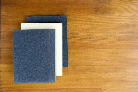 abrasive: Sanding sponge on polishing paper abrasive materials on wooden background. Stock Photo