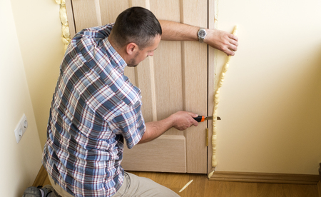 polyurethane: Handyman knife cuts off excess mounting foam. Installation of doors using polyurethane foam mounting. Stock Photo