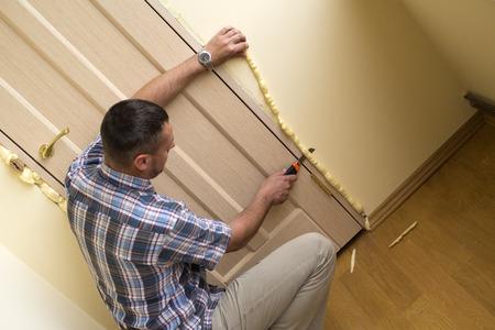 Handyman knife cuts off excess mounting foam. Installation of doors using polyurethane foam mounting. Stock Photo