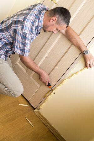 pu foam: Master knife cuts off excess mounting foam. Installation of doors using polyurethane foam mounting.