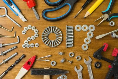 ネジで新年あけましておめでとうございます 2017 組成釘、ボルト、ダボ、木製の背景上のツール 写真素材