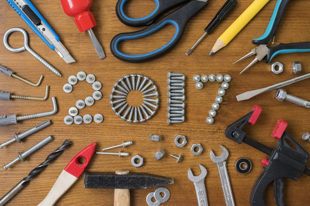 nippers: Happy new year 2017 composition with screws, nails,  bolts , dowels and tools on wooden background