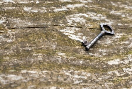 glistening: An vintage skeleton key on an grungy old dark, rustic wood background. Stock Photo