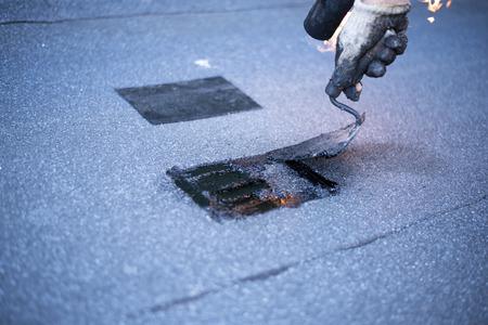 屋根職人、屋根の防水、プロパン バーナーとこてを使用してパッチを溶接修理を行います。ロール屋根防水のインストール。 写真素材 - 58411035