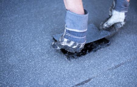 屋根職人、屋根の防水、プロパン バーナーとこてを使用してパッチを溶接修理を行います。ロール屋根防水のインストール。