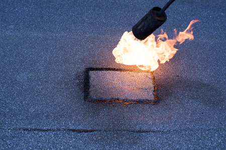 roofing membrane: Roofer making repairs waterproofing of the roof, welding patches by using a propane  gas burner and trowel. Installation of roll roofing waterproofing.