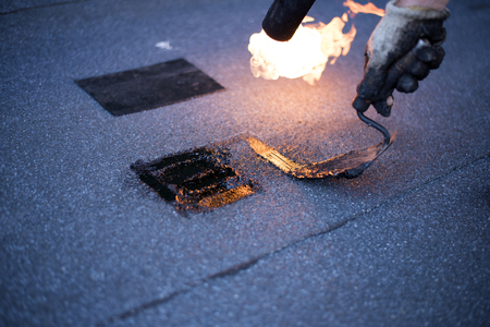 propane gas: Roofer making repairs waterproofing of the roof, welding patches by using a propane  gas burner and trowel. Installation of roll roofing waterproofing.