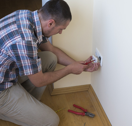 socket outlet: Electrician installing new current socket with screwdriver. Installing electrical outlet or socket - closeup on electrician hands Stock Photo