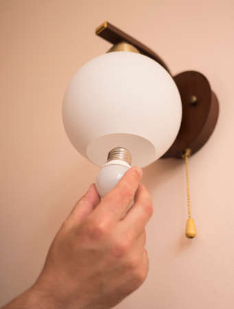 Man changes an electric light bulb, energy efficiency. Closeup of mans hand adjusting electric bulb by pendant lights at home. Stock Photo