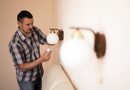 electric fixture: Man changes an electric light bulb, energy efficiency. Closeup of mans hand adjusting electric bulb by pendant lights at home
