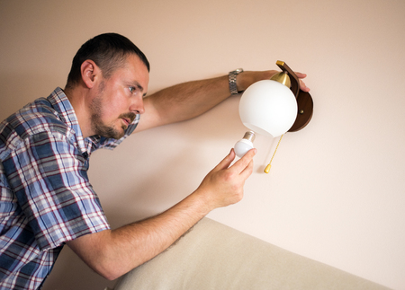 electric bulb: Man changes an electric light bulb, energy efficiency. Closeup of mans hand adjusting electric bulb by pendant lights at home. Stock Photo