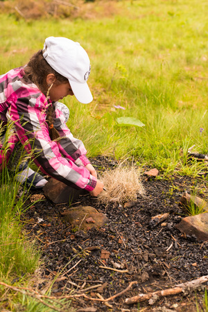 scouting: Starting fire with firesteel. Little girl  lighting a fire in   forest, preparing for an overnight sleep in nature, warming himself with DIY fire. Adventure, scouting, survival concept.
