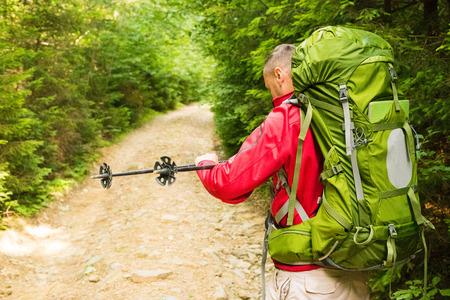 mochila de viaje: turístico atractivo con una gran mochila de viaje regula el poste del senderismo en un sendero de montaña y sonriente, viajero feliz superar un largo camino sonriendo, mirando a un lado, el turismo de aventura y el descubrimiento
