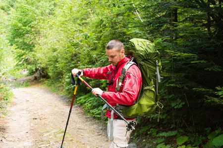 Attractive tourist with a big backpack travel regulates trekking pole on a mountain trail and smiling, happy traveler overcome a long way smiling, looking aside, adventure travel and discovery Banco de Imagens
