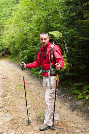 trekking pole: Male hiker with big green traveling rucksack and trekking pole moving up on the mountain trail and smiling, happy traveler overcome big way smiling looking away, adventure travel and discovery Stock Photo