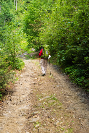 trekking pole: Male hiker with big green traveling rucksack and trekking pole moving up on the mountain trail and smiling, happy traveler overcome big way  looking away, adventure travel and discovery Stock Photo