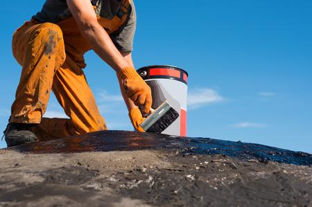 Dakdekker betrekking hebben op de betonnen voet, polymeer gemodificeerde bitumen waterdicht maken primer. Een werknemer borstels dekken beton, bitumen-rubber primer. Stockfoto