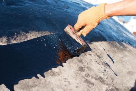 ポリマー改質アスファルト防水プライマー、屋根葺き職人はベースのコンクリートをカバーします。労働者は、かぶりコンクリート、アスファルト ゴム プライマーをブラシします。 写真素材 - 60799676