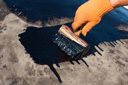 bitumen felt: Roofer cover the concrete base, polymer modified bitumen waterproofing primer. A worker brushes cover concrete, bitumen-rubber primer.