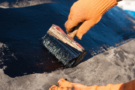 Roofer cover the concrete base, polymer modified bitumen waterproofing primer. A worker brushes cover concrete, bitumen-rubber primer.