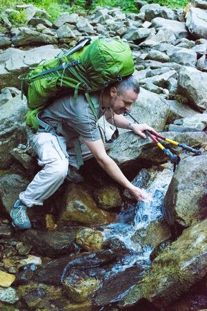 Hiker bending to take a drink from the stream in the mountain. Young hiker with green  rucksack and trekking pole drinking stream water with his hands,  in mountain.