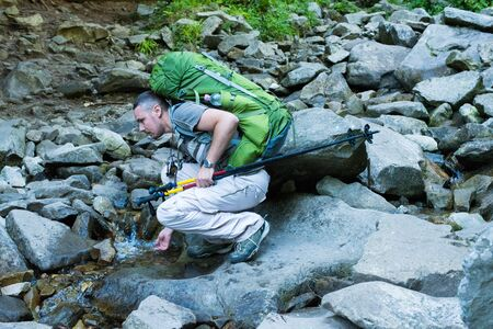Hiker bending to take a drink from the stream in the mountain. Young hiker with green  rucksack and trekking pole drinking stream water with his hands,  in mountain