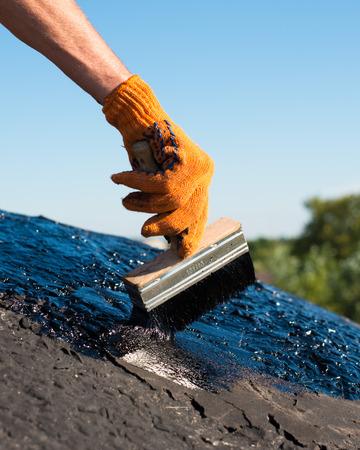 tar felt: Roofer cover the concrete base, polymer modified bitumen waterproofing primer. A worker brushes cover concrete, bitumen-rubber primer.