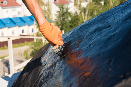 ruberoid: Roofer cover the concrete base, polymer modified bitumen waterproofing primer. A worker brushes cover concrete, bitumen-rubber primer.