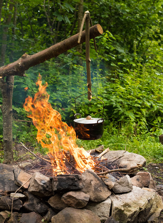 Cooking in the sooty  cauldron on the open fire in woods. Stock Photo