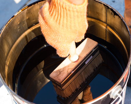 tar felt: Tool for waterproofing. Roofer cover the concrete base, polymer modified bitumen waterproofing primer. A worker brushes cover concrete, bitumen-rubber primer.