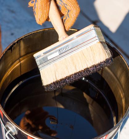 防水のためのツール。ポリマー改質アスファルト防水プライマー、屋根葺き職人はベースのコンクリートをカバーします。労働者は、かぶりコンク