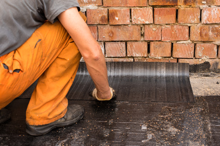 ruberoid: Roofer trying syhment rolled waterproofing. Professional master , making waterproofing. Installation of roll roofing waterproofing propane blowtorch during construction. Stock Photo