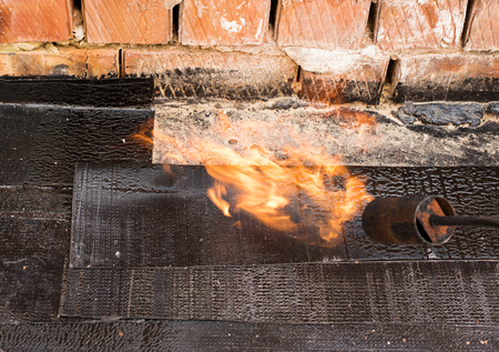 blowtorch: Professional master , making waterproofing. Installation of roll roofing waterproofing propane blowtorch during construction. Fixing waterproof abutment