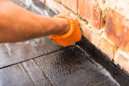 floor covering: Professional master , making waterproofing. Installation of roll roofing waterproofing propane blowtorch during construction. Fixing waterproof abutment