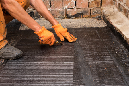 floor covering: Roofer cut a piece of rolled waterproofing.  Professional master , making waterproofing. Installation of roll roofing waterproofing propane blowtorch during construction.