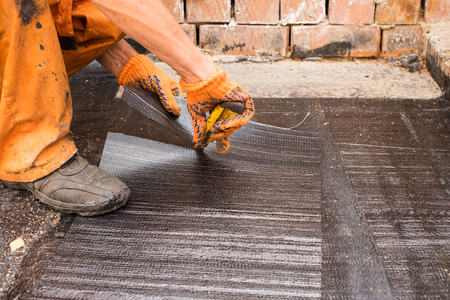 blowtorch: Roofer cut a piece,  of rolled waterproofing.Professional master , making waterproofing. Installation of roll roofing waterproofing propane blowtorch during construction.